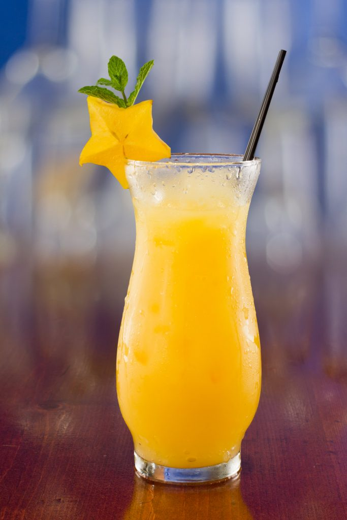 fresh tropical juices mixed and served in a glass decorated with a carambola slice and fresh mint